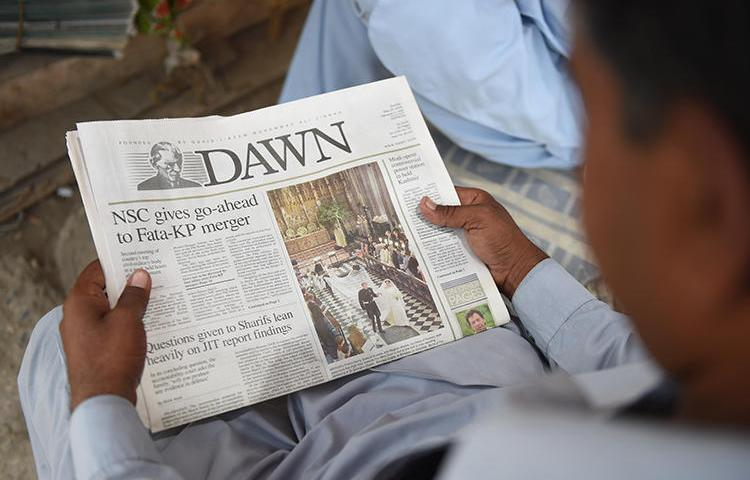 A man reads a copy of the Dawn English-language newspaper in Karachi, Pakistan, on May 20, 2018. Demonstrators recently besieged Dawn's Islamabad offices and threatened its staffers. (AFP/Rizwan Tabassum)