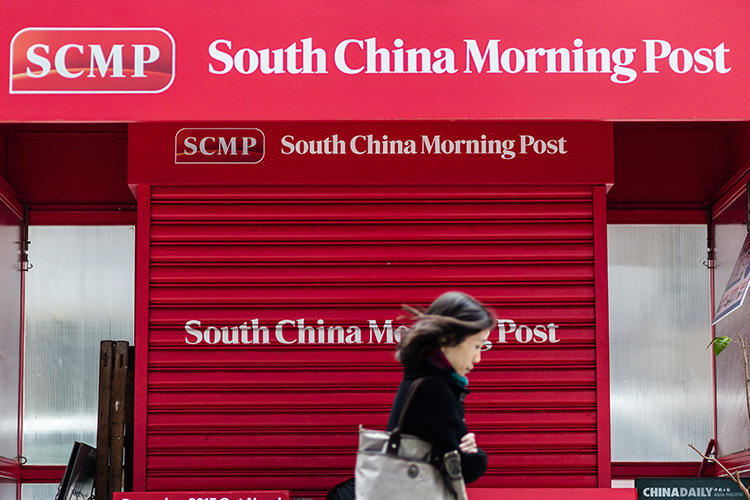 A pedestrian walks past a closed newsstand with the logo of the South China Morning Post (SCMP) in Hong Kong on December 12, 2015, following the acquisition by Chinese internet giant Alibaba of the English-language newspaper. (AFP/Anthony Wallace)