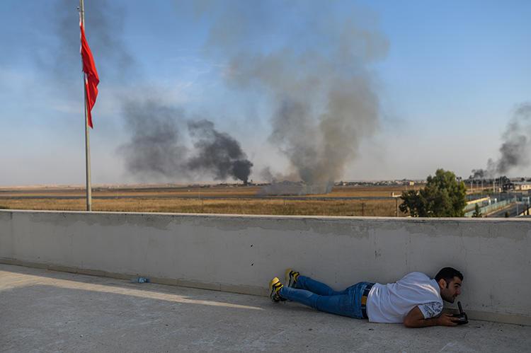 2019年10月10日,土耳其部队挺进叙利亚攻击库尔德武装的第二天,一名记者在土耳其与 叙利亚接壤的阿克恰卡莱(Akcakale) 寻找掩护,一个迫击炮刚降落在附近。2019年, 至少有七名记者在叙利亚殉职,包括在10月土耳其发动的空袭中丧生的三名记者。(法新 社/Bulent Kilic)
