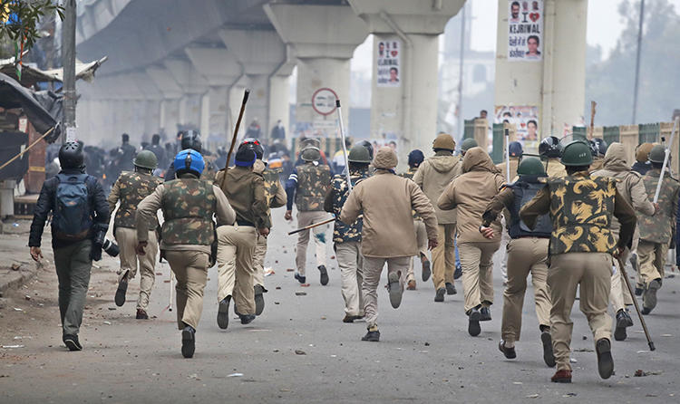 Police officers chase protesters in New Delhi, India, on December 17, 2019. Several journalists have been attacked since the protests began. (AP/Manish Swarup)