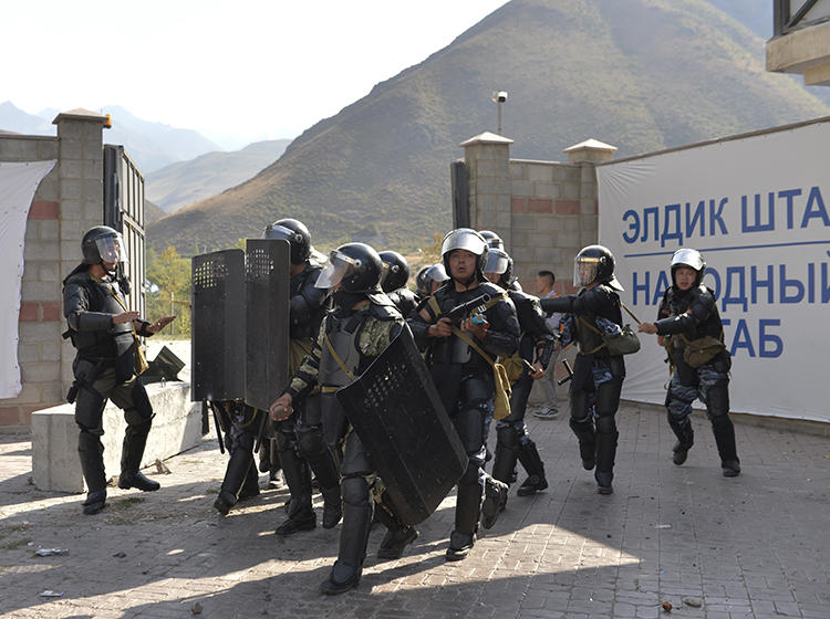 Police officers are seen in Koi-Tash, Kyrgyzstan, on August 8, 2019. CPJ recently joined a letter urging the Kyrgyz government to stop harassing journalists. (AP/Vladimir Voronin)