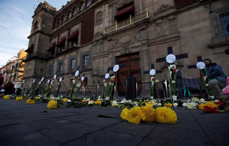 Flores y cruces llevan el nombre de periodistas y personas defensoras de los derechos humanos asesinados en los primeros tres meses de la gestión del presidente Andrés Manuel López Obrador, en febrero de 2019 en Ciudad de México. Como mínimo, dos de los periodistas que fueron asesinados por su labor en 2019, se habían incorporado a un mecanismo de protección. (AP/Rebecca Blackwell)