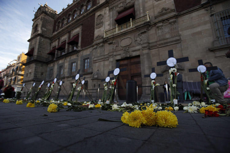 Flowers and crosses bear the names of journalists and human rights defenders murdered in the first three months since President Andrés Manuel López Obrador took office, in Mexico City in February 2019. At least two of the journalists murdered for their work in 2019 were enrolled in a safety protection mechanism. (AP/Rebecca Blackwell)