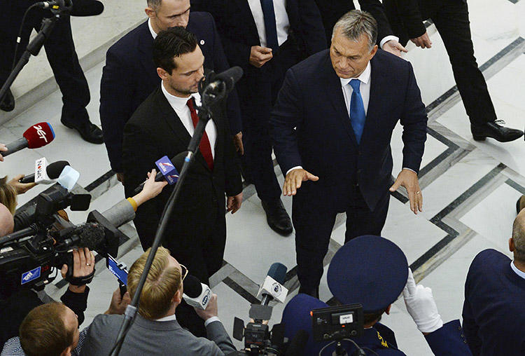 Hungarian Prime Minister Viktor Orbán, right, gestures as he walks past journalists after talks in Warsaw, Poland, in September 2017. A joint mission to Hungary in November 2019 found that the government has pursued a strategy to silence the country's press. (AP/Alik Keplicz)