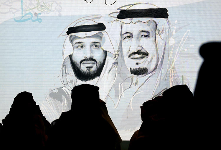 Saudi participants at the Future Investment Initiative stand for the national anthem in front of a screen displaying images of Saudi King Salman, right, and Crown Prince Mohammed bin Salman, on October 28, 2019, in Riyadh. Saudi Arabia had at least 26 journalists in prison at the end of 2019. (AP Photo/Amr Nabil)