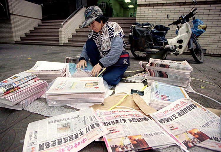 A Taipei newspaper delivery woman counts piles of evening newspapers bearing headlines of Hong Kong's midnight handover to Chinese rule on June 30, 1997. (Reuters)