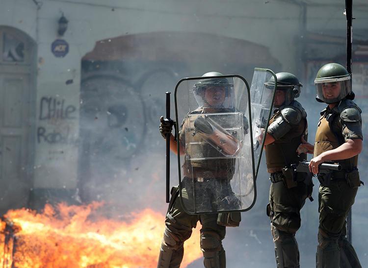 Imagen de agentes policiales frente a una barricada en llamas en Valparaíso, Chile, el 26 de noviembre de 2019. Las oficinas en Valparaíso del diario chileno El Líder fueron saqueadas e incendiadas por manifestantes el 26 de noviembre. (Reuters/Goran Tomasevic)