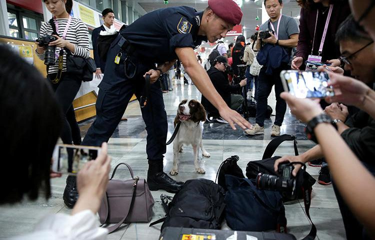 A security officer checks journalists' belongings at Macau International Airport on December 18, 2019. At least three journalists were recently denied entry into the territory. (Reuters/Jason Lee)