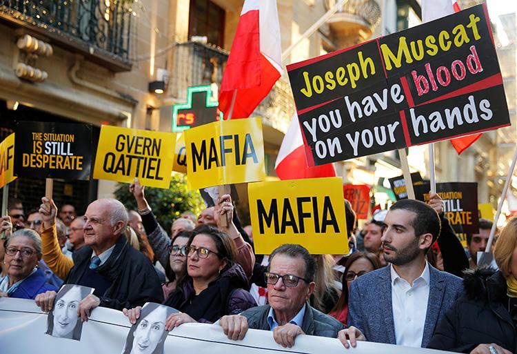1 Aralık 2019 günü, Malta'nın başkenti Valetta'da protestocular gazeteci Daphne Caruana Galzia cinayeti için adalet isteyen bir eylemde pankartlarla görülüyor. (Reuters/Vincent Kessler)