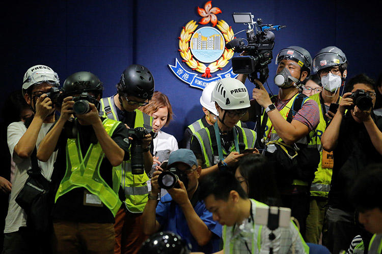 Press photographers in Hong Kong on June 13, 2019, wear helmets and protective masks to a police press conference to protest how police treated journalists during the previous day's demonstration against a proposed extradition bill. (Reuters/Thomas Peter)