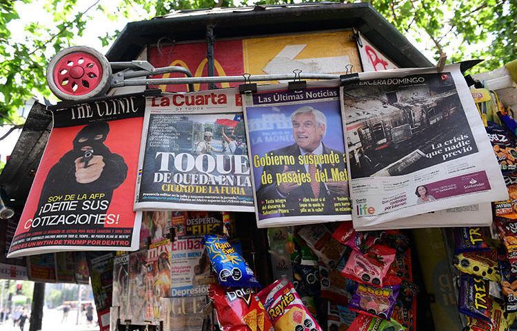 Diarios chilenos son vendidos en Santiago, el 20 de octubre de 2019. Atacantes enmascarados irrumpen en las oficinas del periódico chileno El Mercurio de Antofagasta, dañan equipos y prenden incendios. (AFP/Martin Bernetti)