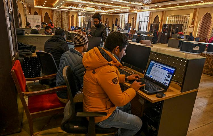 Kashmiri students use the internet at a Tourist Reception Centre in Srinagar on December 3, 2019, amid an internet suspension across the region as part of a partial communication blockade by the Indian government. Despite a Supreme Court ruling in January 2020, internet access has only been partially restored, and many news outlets remain offline. (AFP/Tauseef Mustafa)