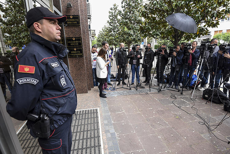 Journalists and law enforcement are seen in Podgorica, Montenegro, on May 9, 2019. Montenegro authorities recently arrested journalist Anđela Đikanović and charged her with incitement. (AFP/Savo Prelevic)