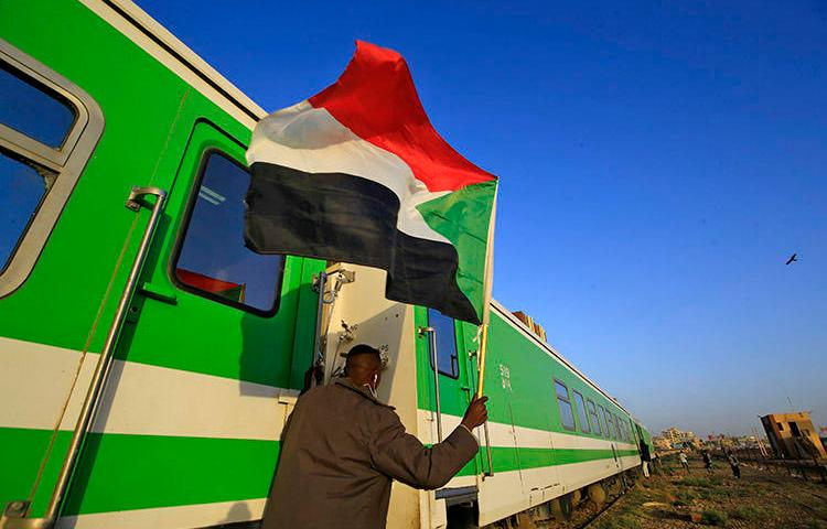 Sudanese protesters wait at a railway station in Khartoum on December 19, 2019 ahead of celebrations of the one-year anniversary of a protest movement that ousted the president. The transitional government in January suspended four news outlets over alleged links to the previous regime. (AFP/Ashraf Shazly)