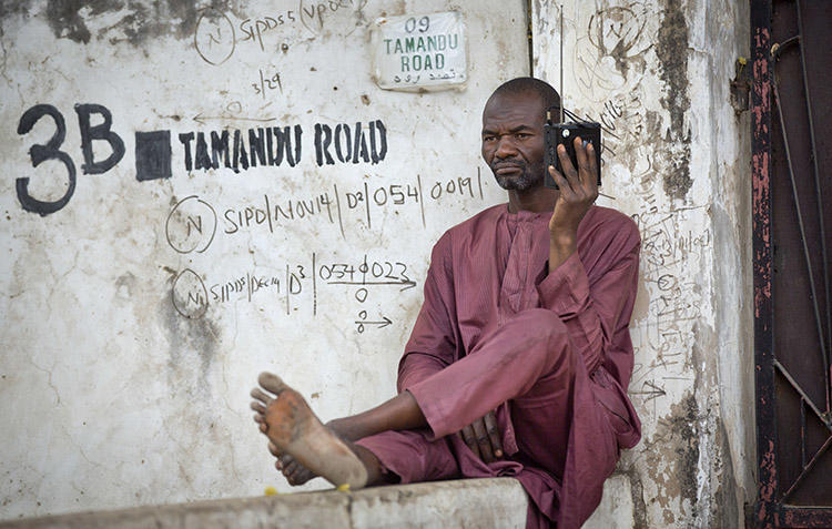 A man listens to a portable radio in Kano, northern Nigeria in 2015. Police in Nigeria's Adamawa State are investigating after a radio journalist was attacked and killed on January 15. (AP/Ben Curtis)
