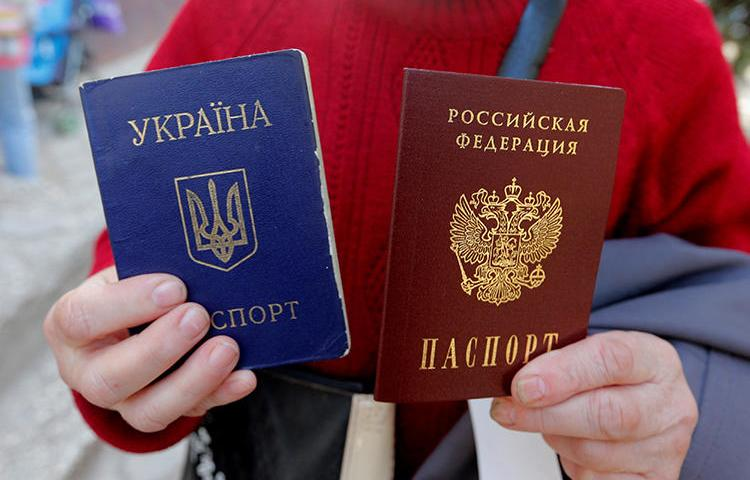 A woman poses with a Ukrainian and a Russian passport in the Crimean city of Simferopol on April 7, 2014. Ukrainian journalist Taras Ibragimov was recently barred from entering Crimea and was banned from entering Russia for 34 years. (Reuters/Maxim Shemetov)