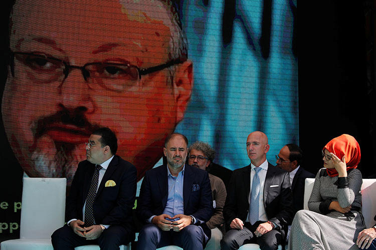 Hatice Cengiz, fiancee of the murdered Saudi journalist Jamal Khashoggi, and Jeff Bezos, founder of Amazon and owner of The Washington Post, are flanked by attendees at a ceremony marking the first anniversary of Khashoggi's killing at the Saudi Consulate in Istanbul, Turkey, on October 2, 2019. (Reuters/Umit Bektas)
