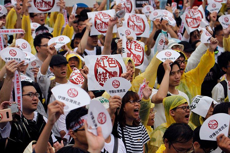 2019年6月23日,抗議者聚集在台北總統府大樓前,手舉「反對紅色媒體」和「守護台灣民主」的海報,抵制親共媒體。(法新社/ Hsu Tsun-hsu)