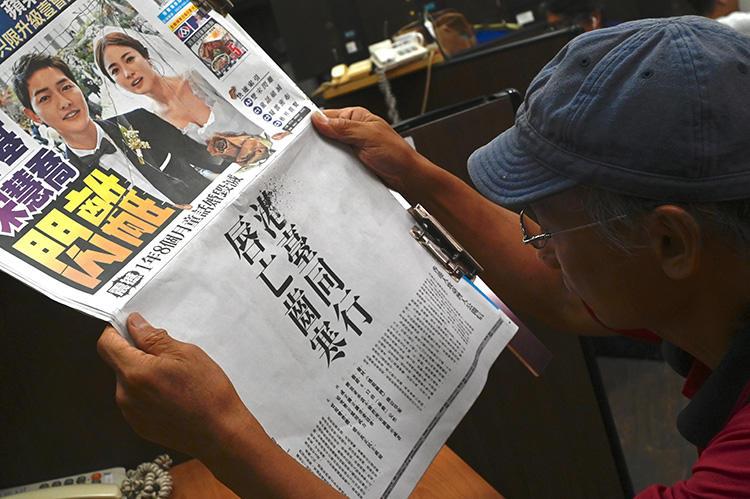 2019年6月28日,一名記者在台北閱讀《蘋果日報》上刊登的一則廣告,該廣告由某香港活動組織投放,呼籲台灣聲援香港,反對送中。(法新社/ Sam Yeh)