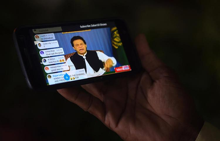 A Pakistani man watches a broadcast by Prime Minister Imran Khan on a smartphone in August 2018. Pakistani regulators are moving to regulate internet videos in measures that journalists fear will result in censorship or penalties. (AFP/Rizwan Tabassum)