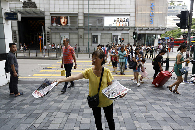 2019年7月7日,香港一名女士在備受大陸遊客歡迎的商業區分發報紙,其頭版新聞標題為《百萬人抗共震驚全球》。(美聯社/ Andy Wong)