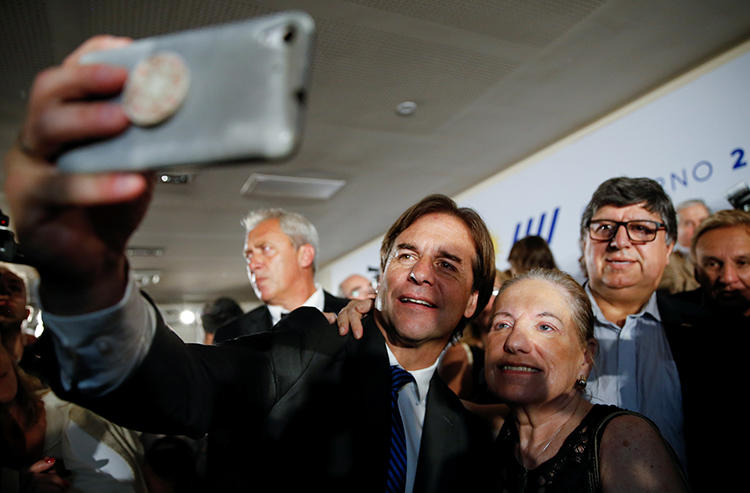 "Uruguayan President-elect Luis Lacalle Pou takes a selfie during the announcement of his incoming cabinet, in Montevideo, Uruguay, in December 2019. His party is seeking to introduce the ""right to be forgotten"" in a hasty legislative process, raising press freedom concerns. (Reuters/Mariana Greif)"