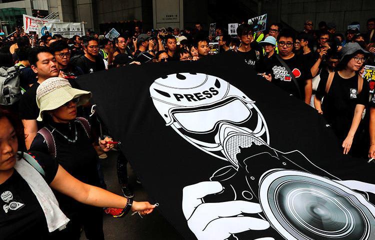 2019年7月4日,香港記者和新聞自由捍衛者發起靜默遊行前往警察總部,譴責警方在反引 渡法案抗議活動中對新聞工作者施暴。(路透社/ Tyrone Siu)