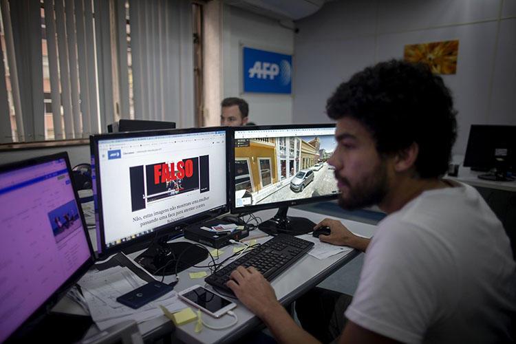 Um jornalista da equipe de verificação de fatos da AFP trabalha no escritório da agência France-Presse, no Rio de Janeiro, Brasil, em 27 de setembro de 2018. Em 11 de fevereiro de 2020, a jornalista brasileira Patrícia Campos Mello enfrentou uma campanha de assédio online após alegações feitas durante uma audiência no Congresso sobre notícias falsas. (AFP / Maruo Pimentel)