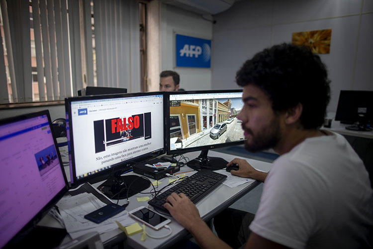 An AFP fact-checking team journalist works at Agence France-Presse Bureau in Rio de Janeiro, Brazil, on September 27, 2018. On February 11, 2020, Brazilian journalist Patrícia Campos Mello faced online harassment campaign after allegations made during a congressional hearing on fake news. (AFP/Maruo Pimentel)
