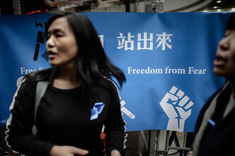 2014年2月28日,幾名香港女士站在桌邊的一條橫幅旁,為聲援自由派《明報》前總編劉進圖收集簽名。襲擊劉進圖的幕後元兇至今未知。(法新社/ Philippe Lopez)