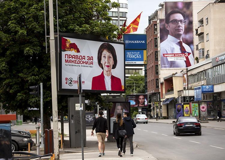 People walk under political billboards in Skopje, North Macedonia, on May 4, 2019. A North Macedonian government official recently threatened two journalists. (AFP/Robert Atanasovski)
