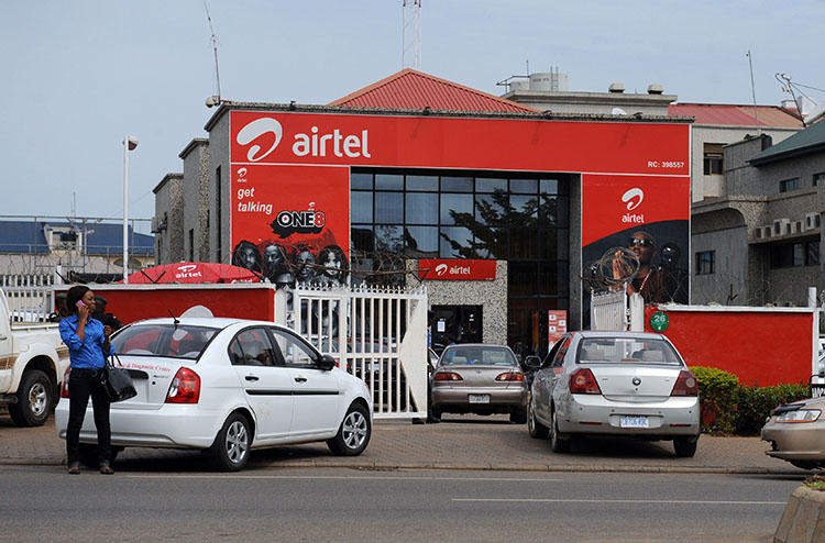 A woman makes a phone call in front of India-owned Airtel on October 10, 2011 in Abuja. A Nigerian NGO on February 25, 2020, sued the Nigerian Communications Commission over warrantless access to 'call data.' (AFP/Pius Utomi Ekpei)