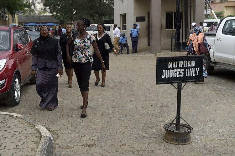 People walk at the premises of Lagos State High Court on January 29, 2019. Nigerian journalist Fejiro Oliver faces cybercrime charges in Lagos for a corruption report. (AFP/Pius Utomi Ekpei)