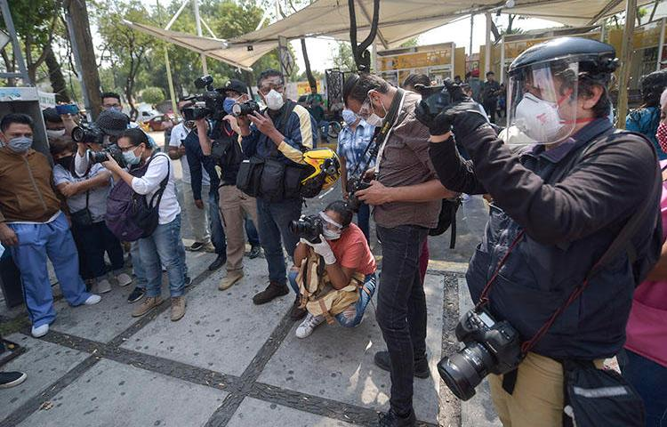 Mexican journalists, wearing personal protective equipment amid the COVID-19 pandemic, cover a protest by administrative workers at the General Balbuena Hospital in Mexico City on April 16, 2020. (AFP/Pedro Pardo)