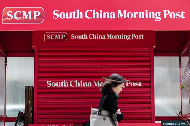 2015年12月12日,在中國電商巨頭阿里巴巴收購英文報紙《南華早報》後,一位行人路過一家關門的報攤,門上印有《南華早報》的商標。(法新社/ Anthony Wallace)