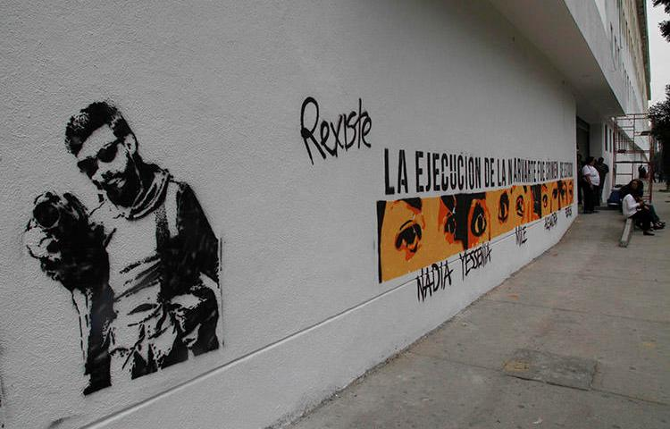 Graffiti shows the likeness of murdered photojournalist Rubén Espinosa and the eyes and names of the other four victims, on the wall of Mexico City attorney general's headquarters in Mexico City, in July 2016. Deadly violence against journalists is rare in the capital, but reporters covering organized crime in the city say threats are on the rise. (AP/Marco Ugarte)