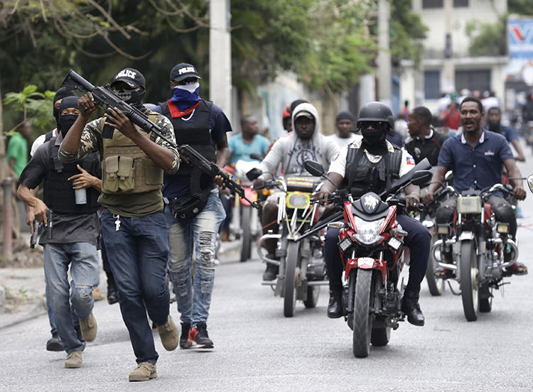 Armed off-duty police officers protest in Port-au-Prince, Haiti, on February 23, 2020. People identifying themselves as police officers committed an arson attack against local broadcaster Radio Télévision Caraïbes. (AP/Dieu Nalio Chery)