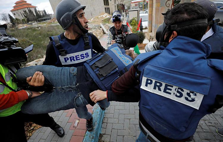 A wounded Palestinian photojournalist is evacuated during a protest in the Israeli-occupied West Bank on February 2, 2020. (Reuters/Mussa Qawasma)