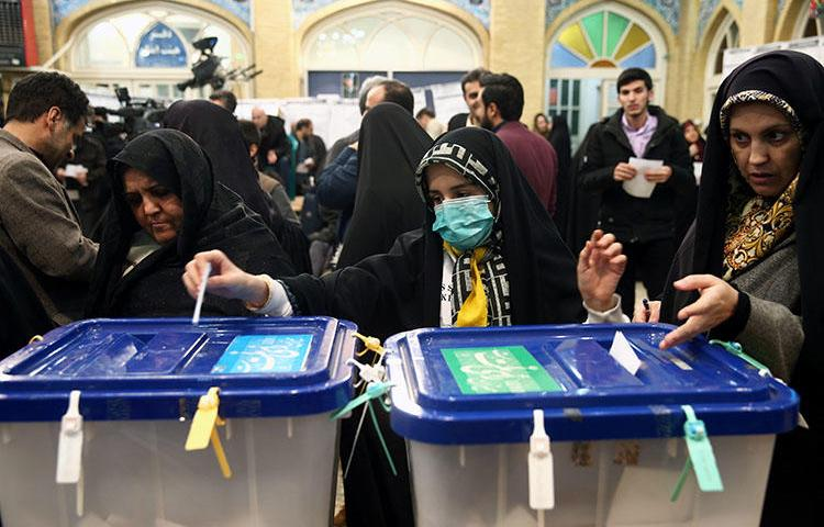 A woman wears a face mask as she casts her vote during parliamentary elections at a polling station in Tehran, Iran February 21, 2020. Iranian authorities detained journalist Mohammad Mosaed the next day for his social media posts. (Nazanin Tabatabaee/West Asia News Agency via Reuters)