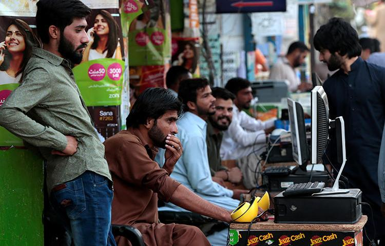 People using computers are seen in Islamabad, Pakistan, on October 20, 2017. The country secretly passed regulations that restrict social media activity. (Reuters/Caren Firouz)