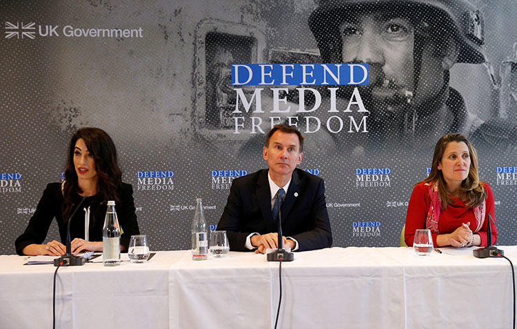 Human rights lawyer Amal Clooney, British then-Foreign Secretary Jeremy Hunt, and Canadian then-Foreign Minister Chrystia Freeland address a news conference on media freedom in Dinard, France on April 5, 2019. A panel of legal experts led by Clooney recommend more sanctions targeted at press freedom violators. (Reuters/Stephane Mahe)