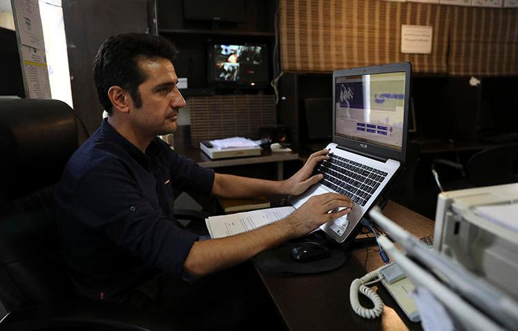 An internet cafe manager works on his computer in Tehran, Iran on July 25, 2019. Iranian journalists say monitored connections and technology companies' concerns about U.S. government sanctions are making it harder for them to bypass censorship. (AP/Vahid Salemi)