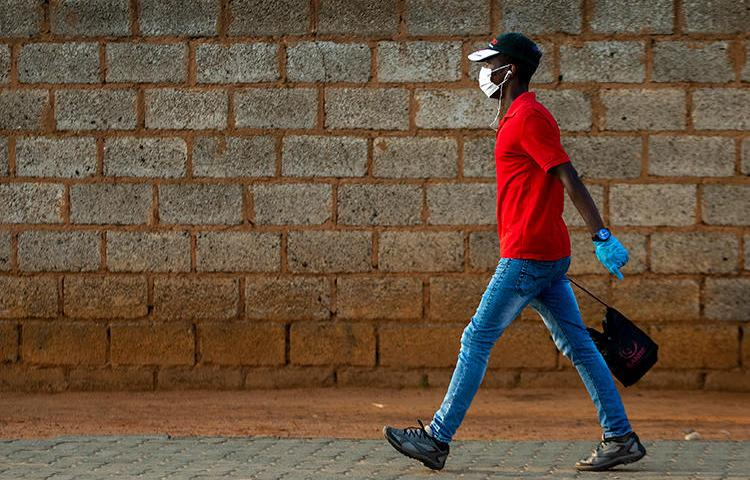 A man wearing a surgical mask and gloves to protect himself from the coronavirus, walks on a street in Soweto, South Africa, Thursday, March 19, 2020. For most people the virus causes only mild or moderate symptoms. For others it can cause more severe illness, especially in older adults and people with existing health problems. (AP/Themba Hadebe)
