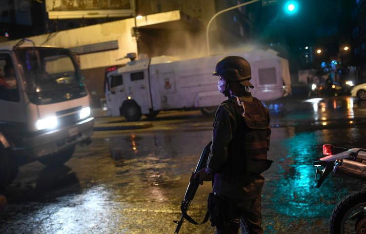 La Guardia Nacional Bolivariana usa un cañón de agua para rociar desinfectante como una medida preventiva contra el contagio del nuevo coronavirus, en Caracas, Venezuela, el 21 de marzo de 2020 (AP/Matias Delacroix)