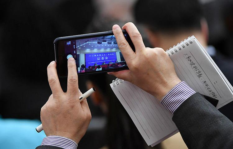 A journalist uses a phone to take photos during a National People's Congress press conference in Beijing in March 2019. The Foreign Correspondents' Club of China annual survey finds conditions for the foreign press deteriorated in 2019. (AFP/Wang Zhao)