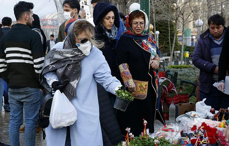 An Iranian woman wearing a protective face mask chooses traditional items ahead of Nowruz, the national New Year celebration, at the Tajrish Bazaar in the capital Tehran on March 19, 2020, despite the heavy death toll due the novel coronavirus in the country. Amid the coronavirus pandemic, the government has covered up crucial information and threatened journalists. (AFP/Stringer)