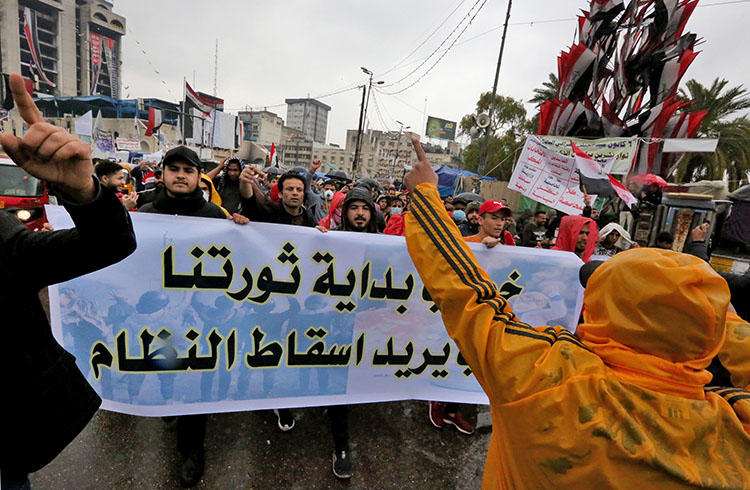 Iraqi protesters lift a banner n Tahrir Square in the capital Baghdad on February 25, 2020, amid renewed anti-government demonstrations. An Iraqi journalist was kidnapped in Baghdad on March 9. (AFP/Sabah Arar)