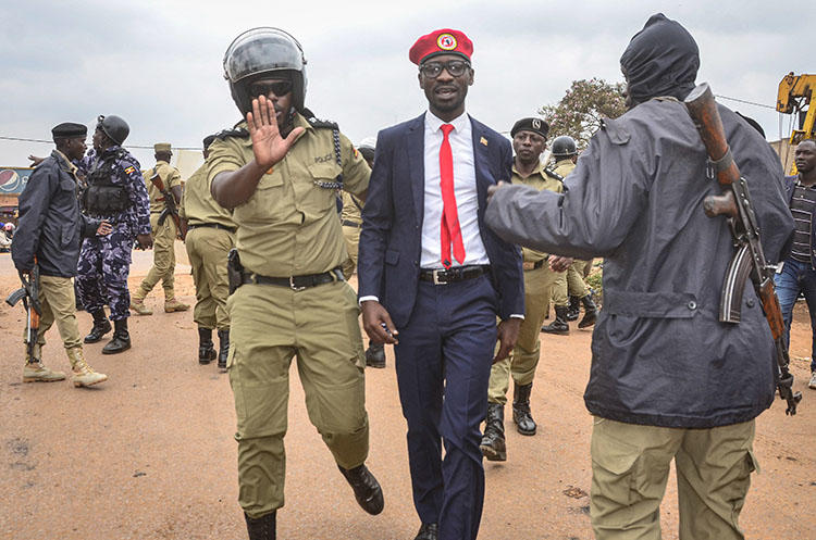 Ugandan opposition politician and popular musician Robert Kyagulanyi, also known as Bobi Wine (C), is escorted by a police officer as he is arrested on charges of unlawful assembly before starting his first public meeting ahead of presidential election next year, on January 6, 2020, in Kasangati town, a suburb of Kampala. Ugandan journalist Moses Bwayo was charged with illegal assembly and held in prison on March 4. (AFP/Stringer)