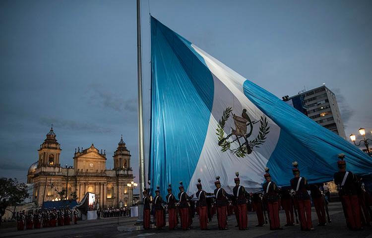 Soldados guatemaltecos izan la bandera nacional en la Plaza de la Constitución, Ciudad de Guatemala, en septiembre de 2019. Con la toma de posesión de un nuevo mandatario, el país tiene la oportunidad de mejorar las condiciones para el ejercicio del periodismo. (AP/Oliver de Ros)