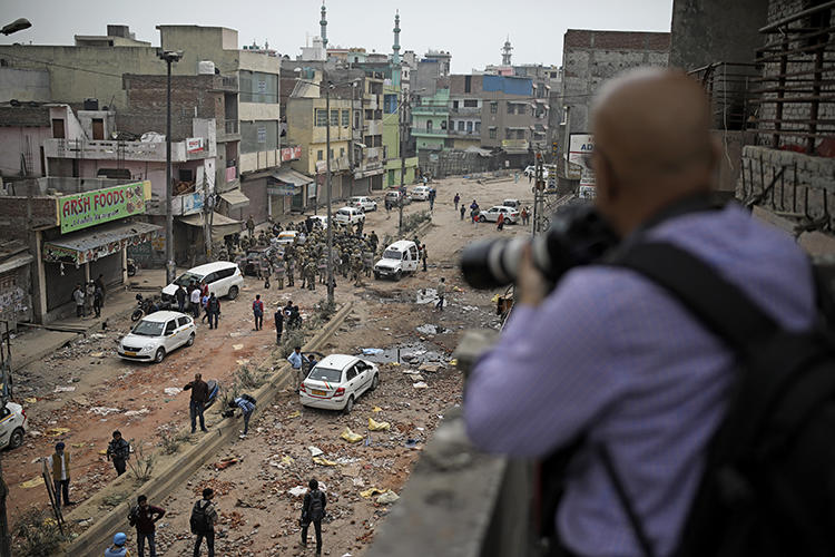A journalist photographs soldiers patrolling a street following riots in New Delhi, India, on February 27, 2020. At least a dozen journalists were attacked or harassed covering the riots. (AP/Altaf Qadri)